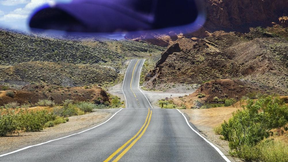 grey concrete road toward brown hills