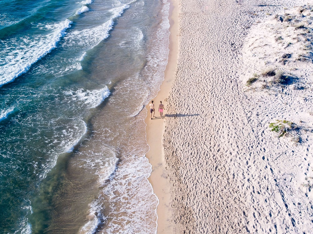 aerial photography of two person walking on seashore during daytime