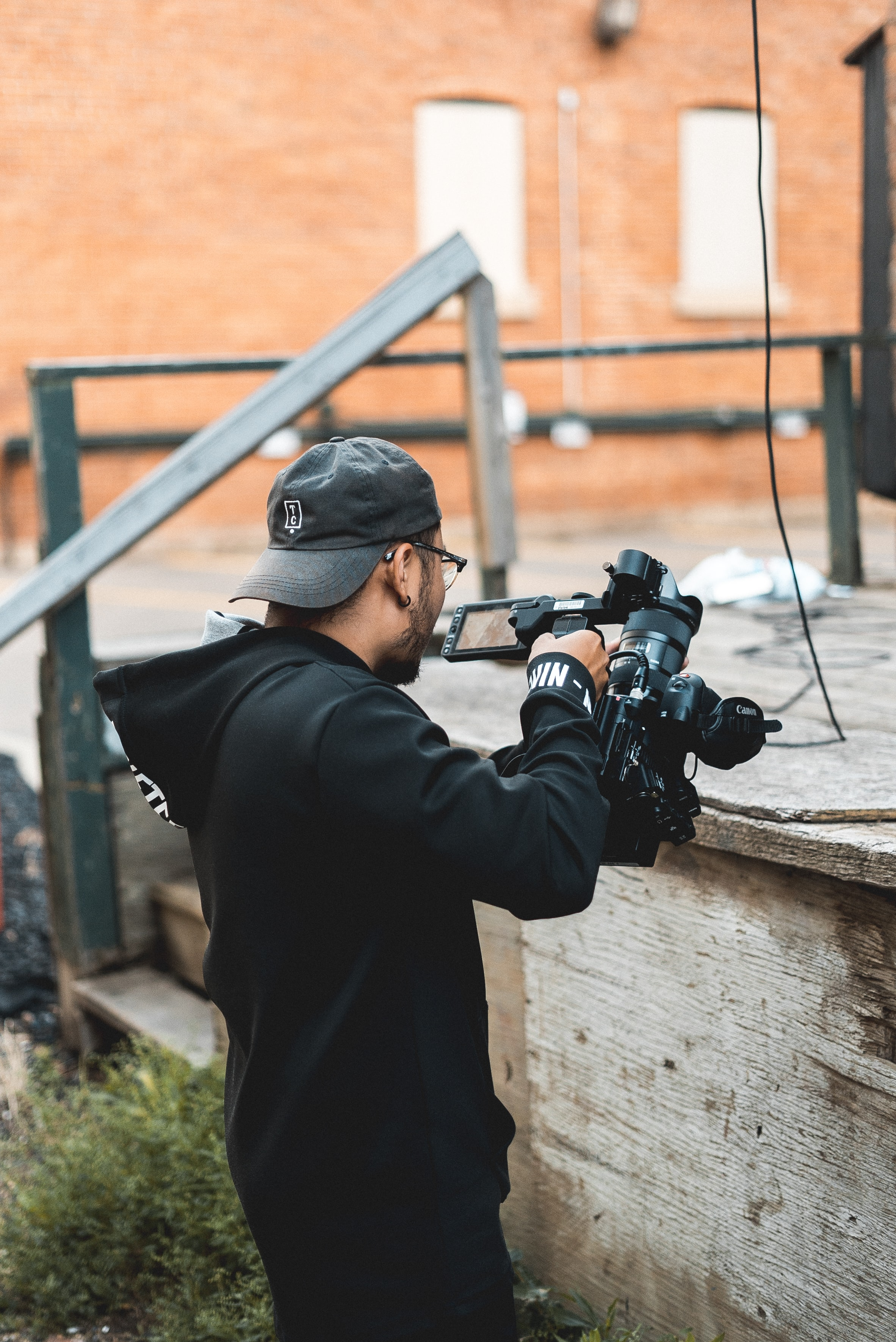 man carrying black video camera during daytime