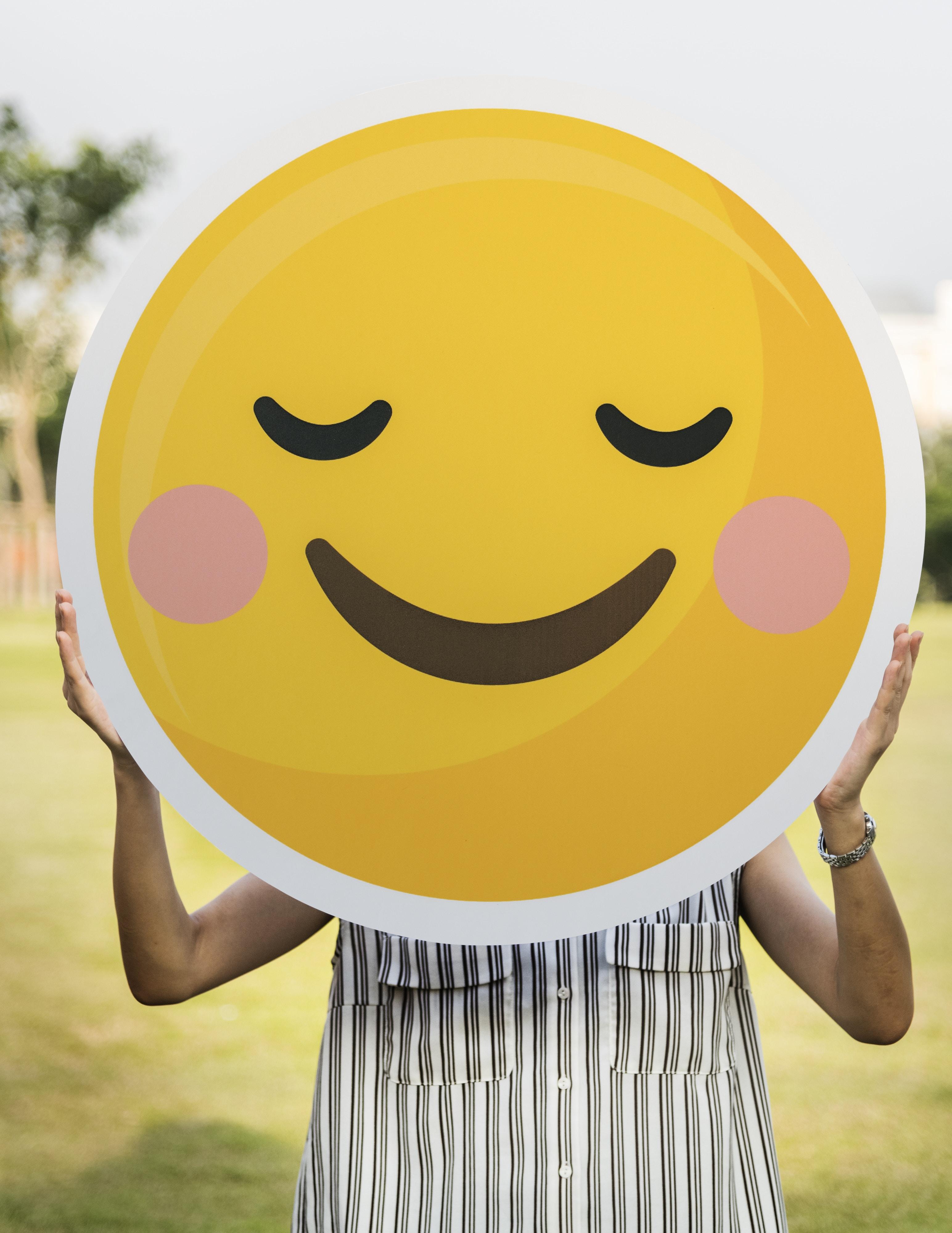 woman holding blush emoticon during daytime