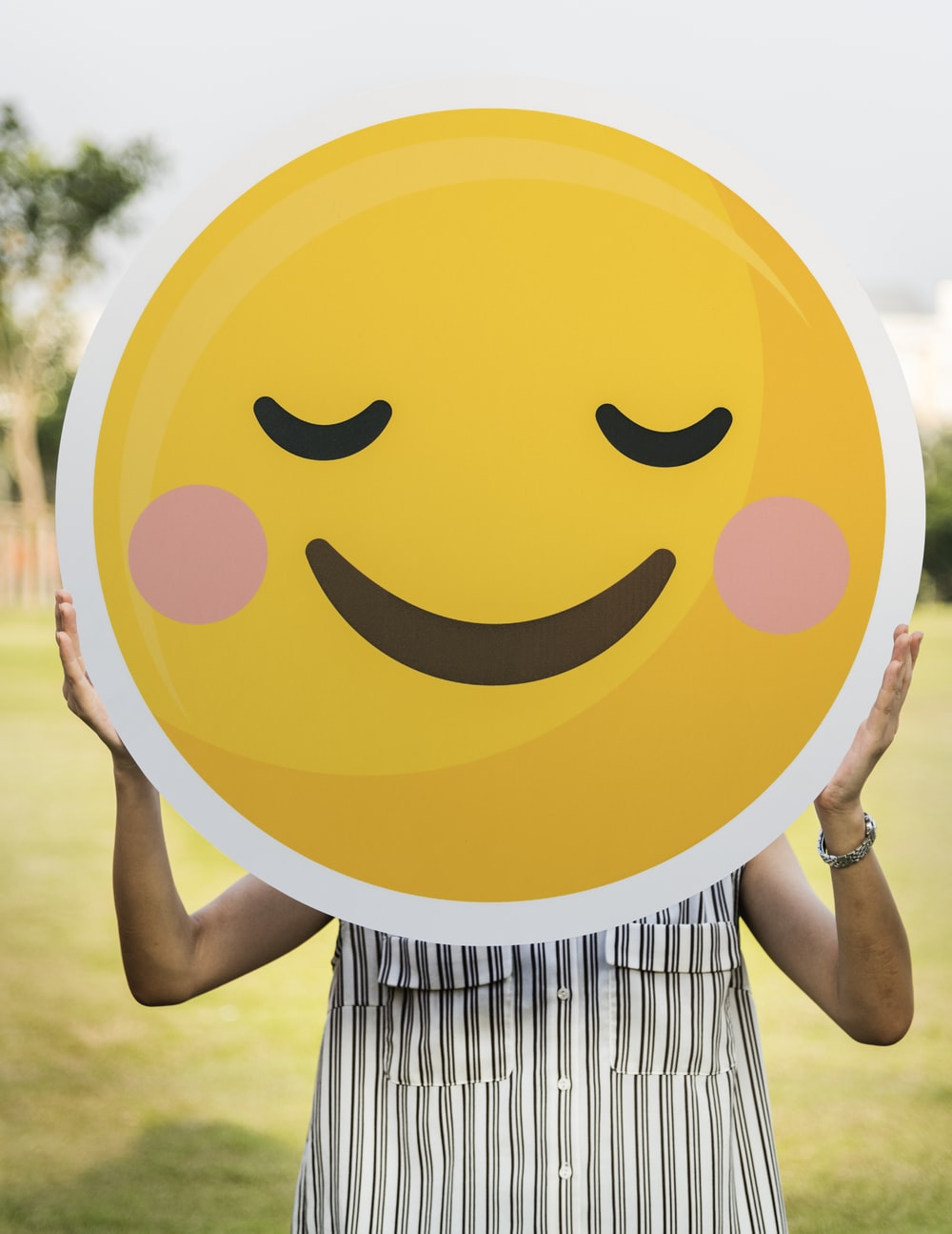 woman holding blush emoticon during daytime