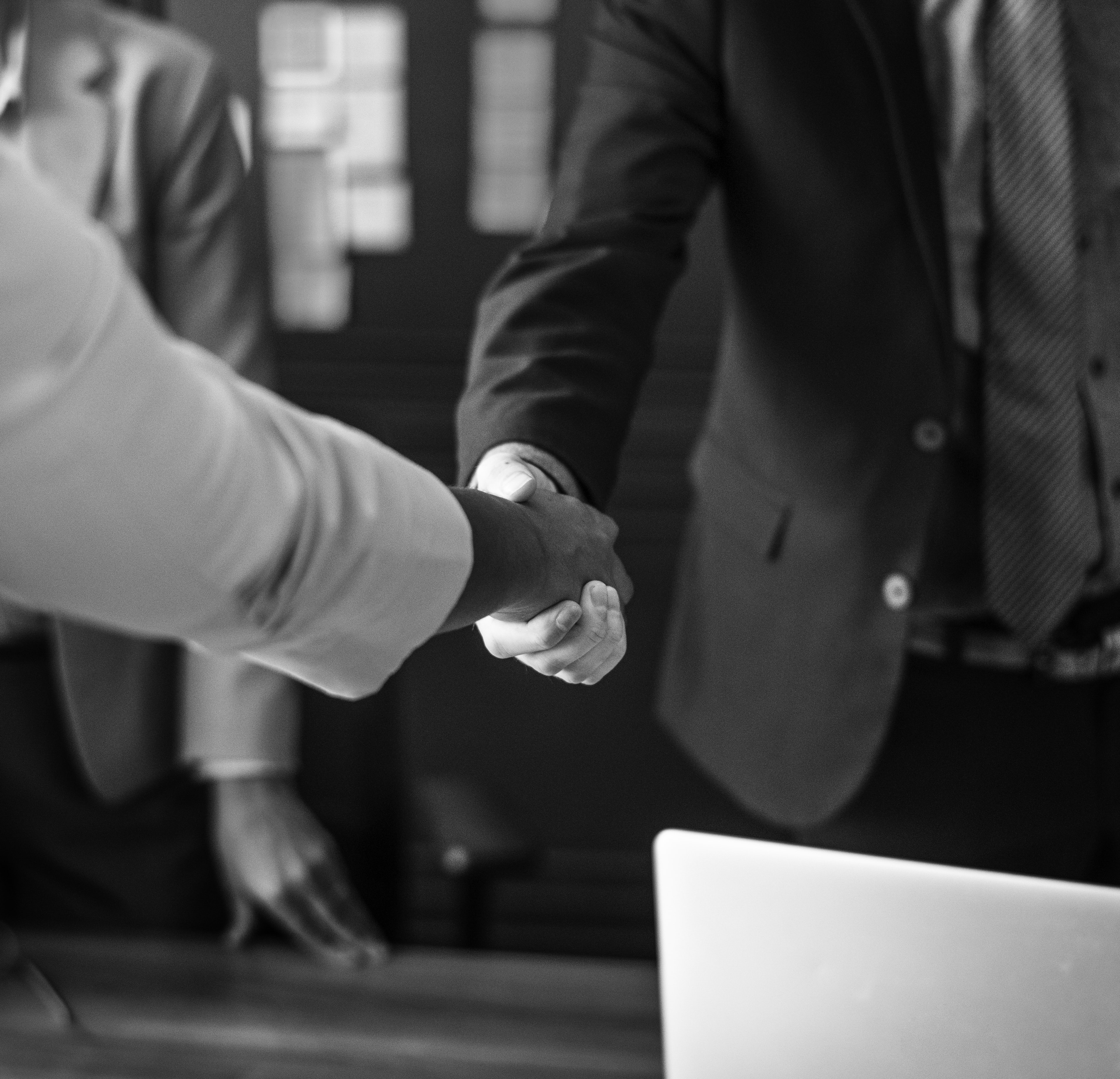 two person shaking hands in grayscale photo