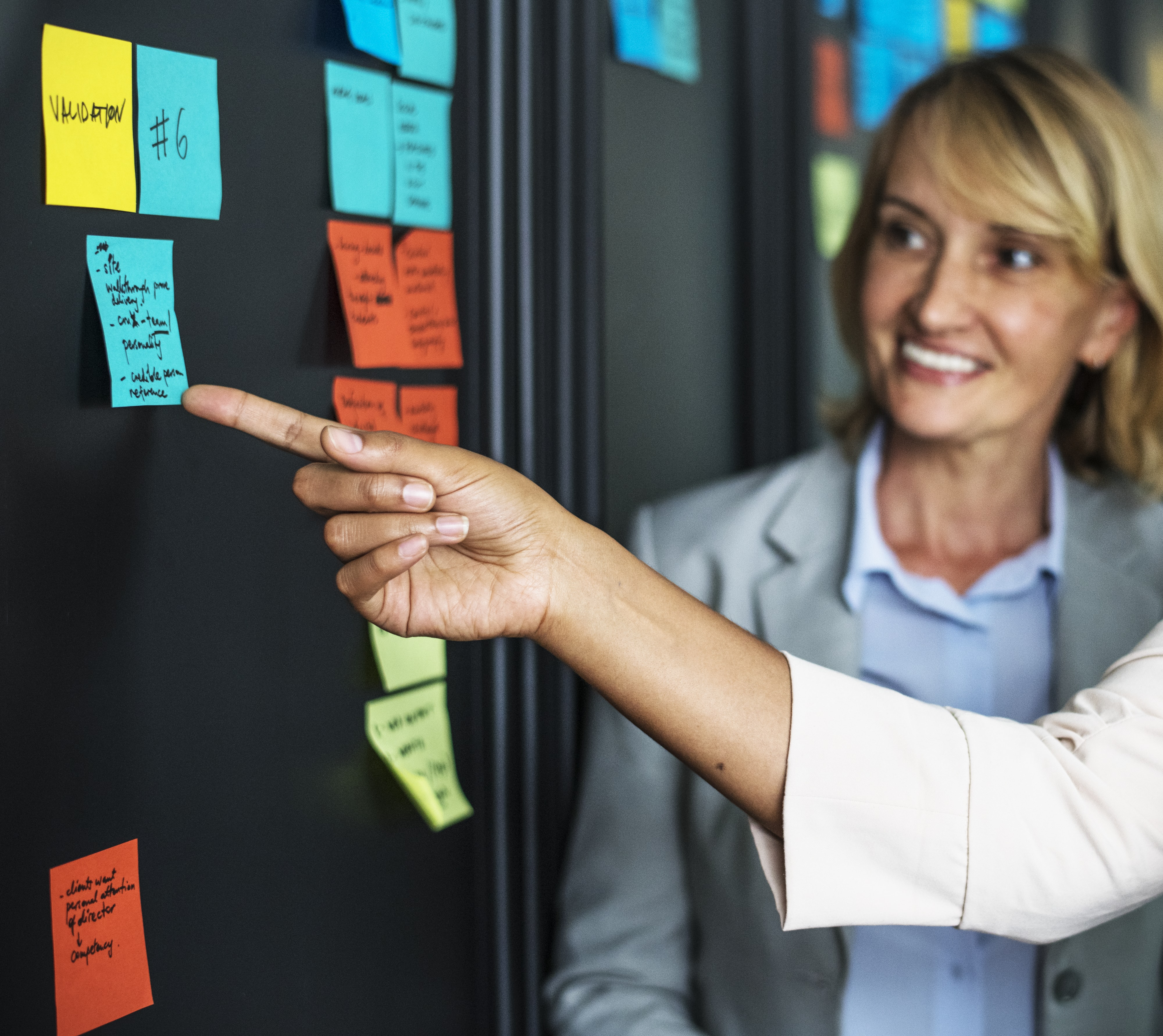 person pointing at blue sticky note on wall