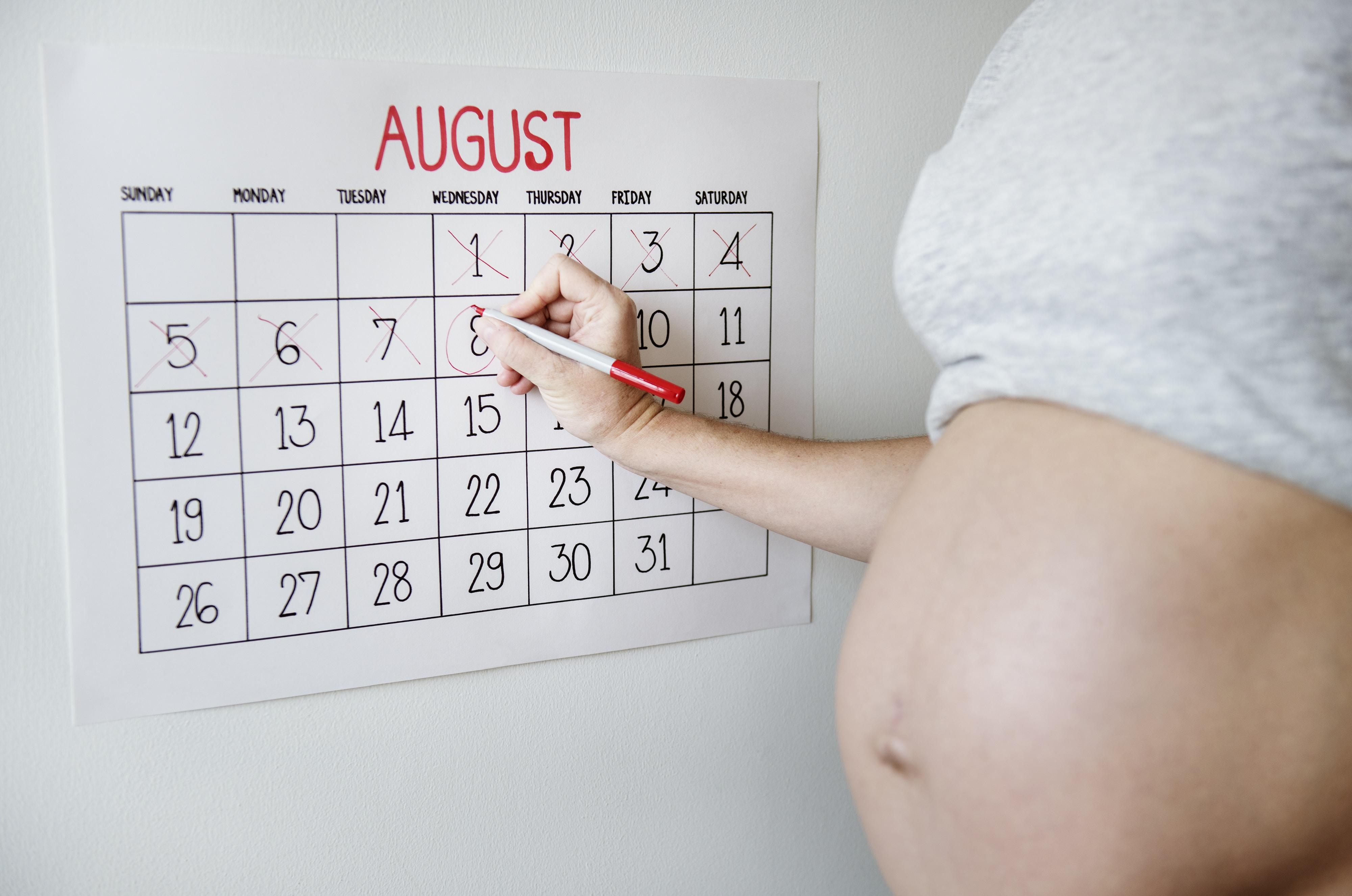 pregnant woman marking August 8 calendar