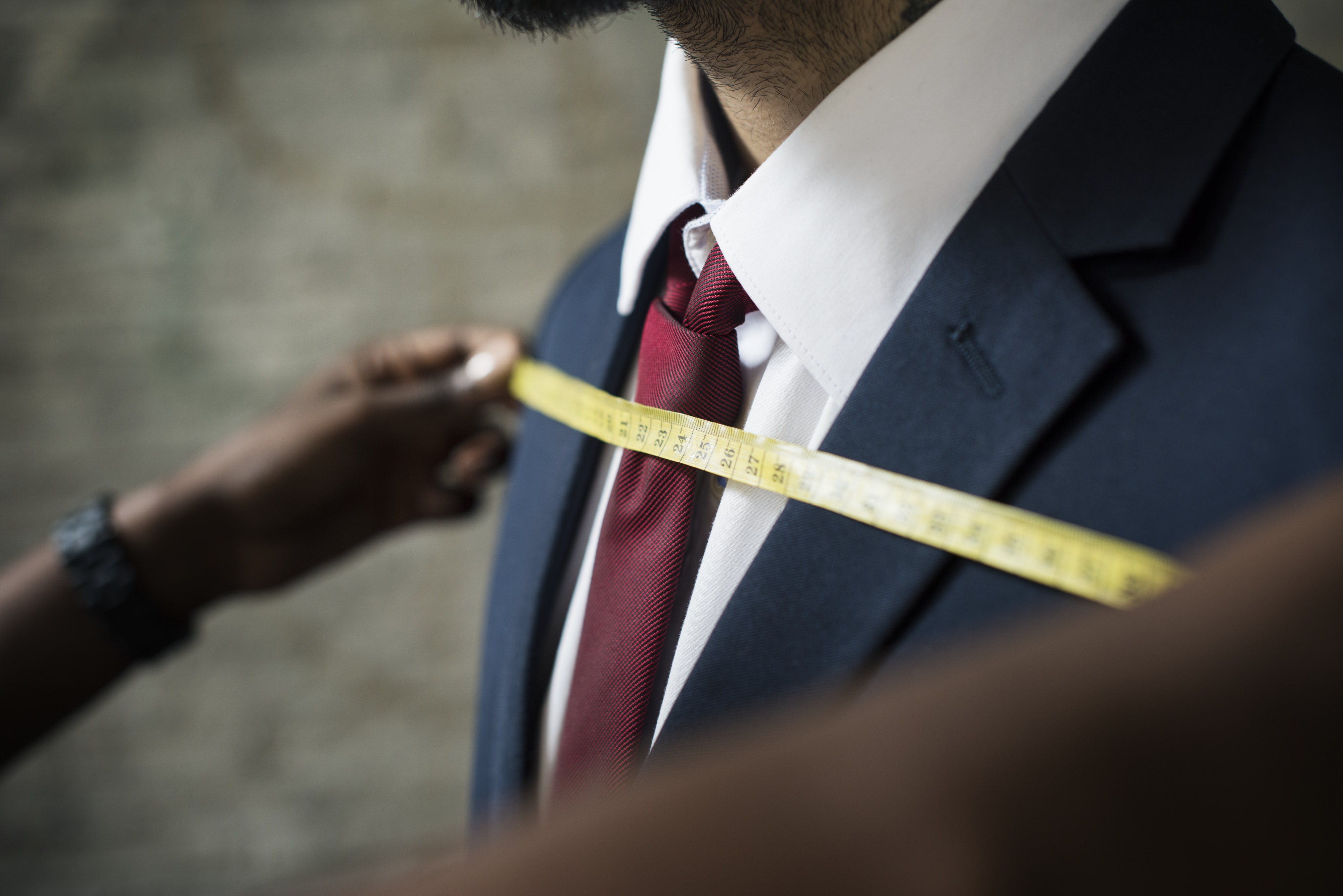 man wearing black suit with measuring tape