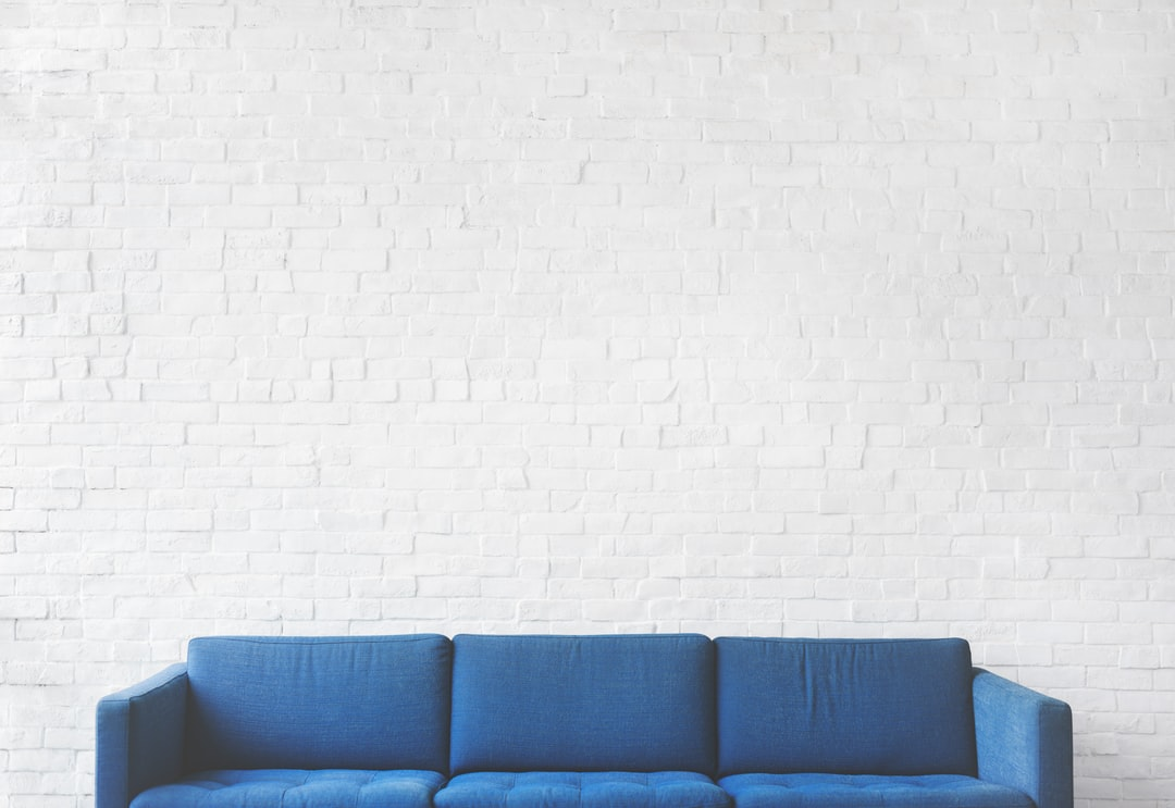 blue 3-seat sofa near white brick wall