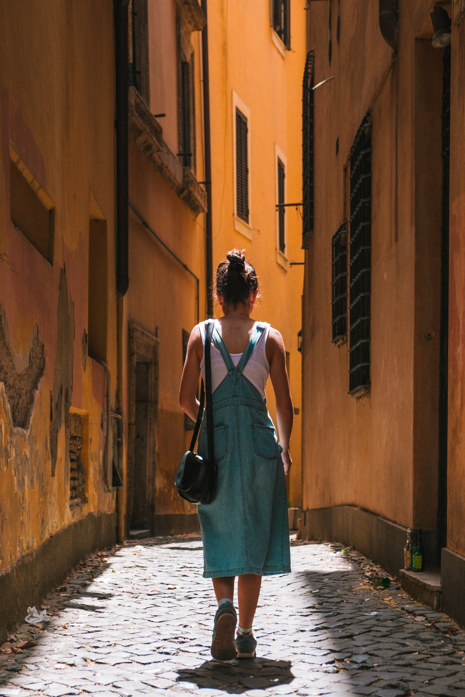 woman in dress walking on alley