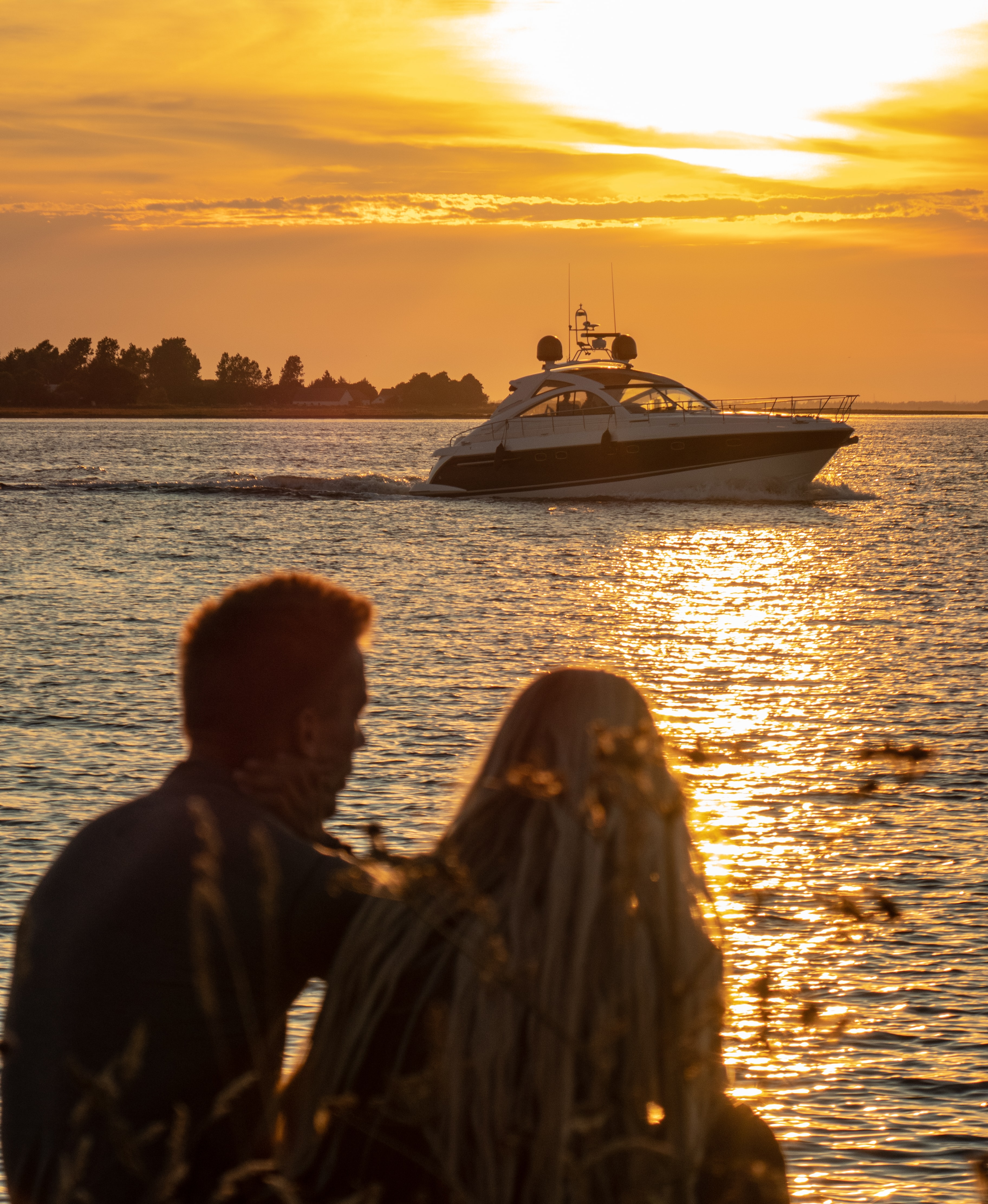 man and woman watching sunset by the sea with view of cabin cruiser