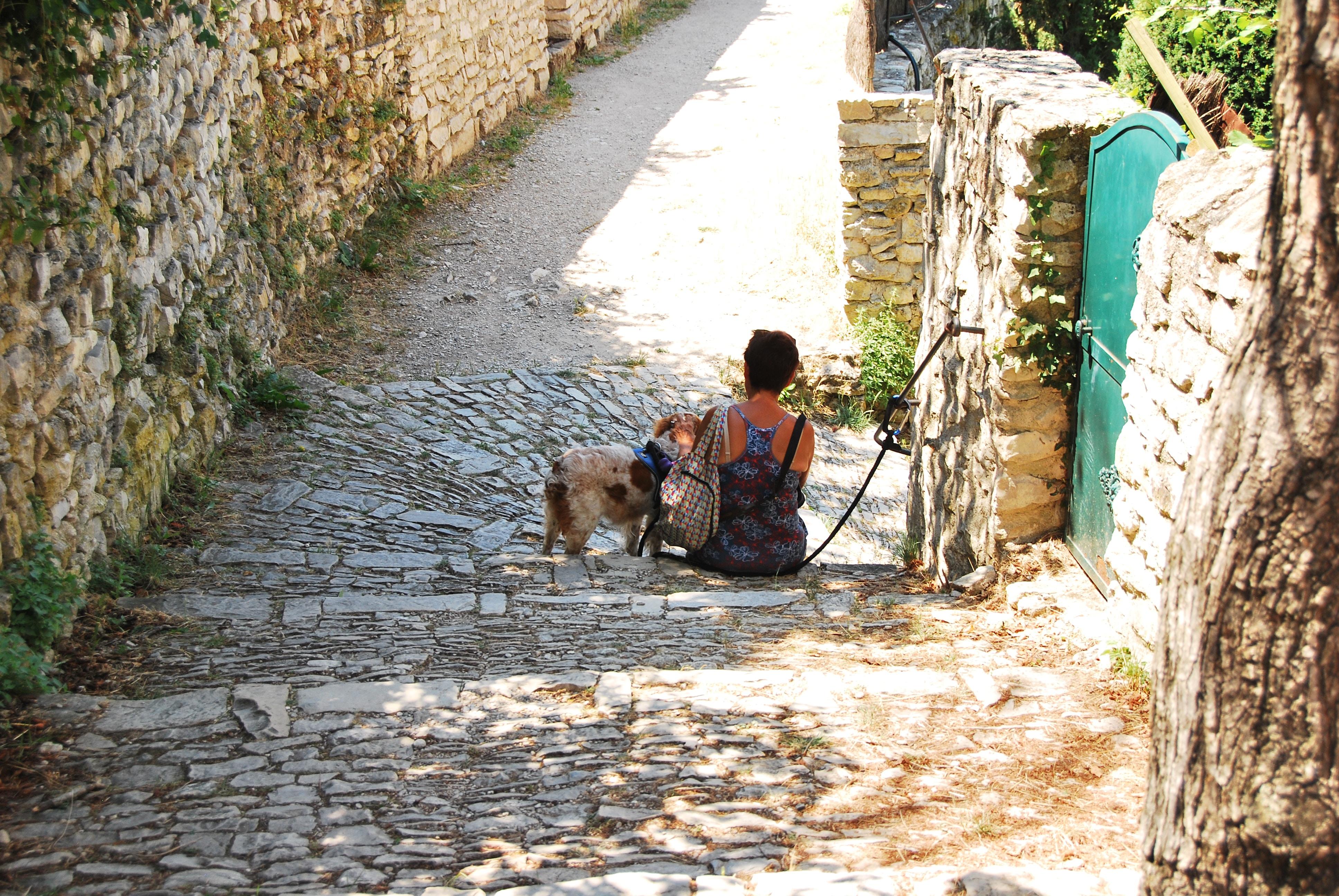 man sitting on gray pathway during daytime