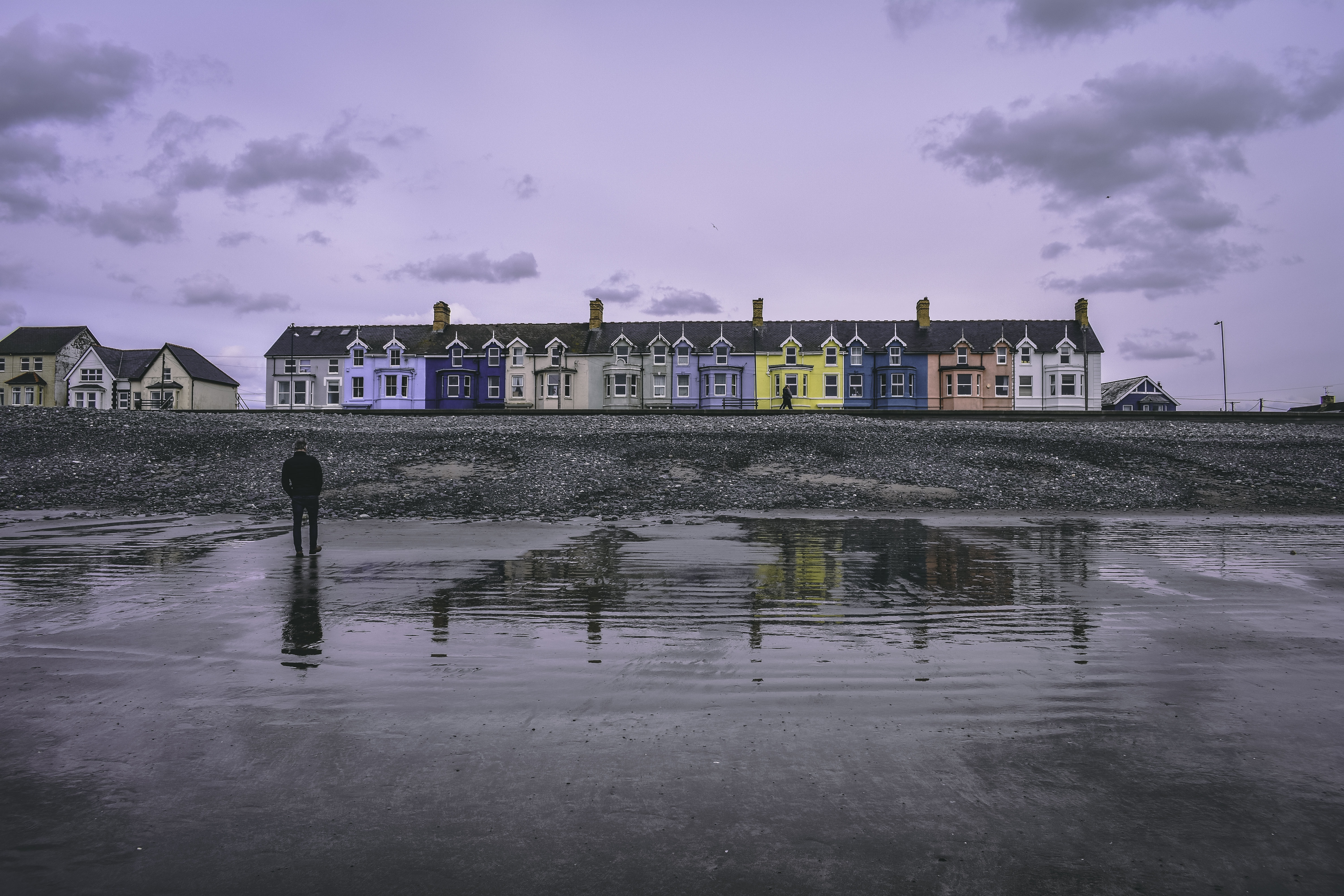 man standing on puddle facing multicolored building during day