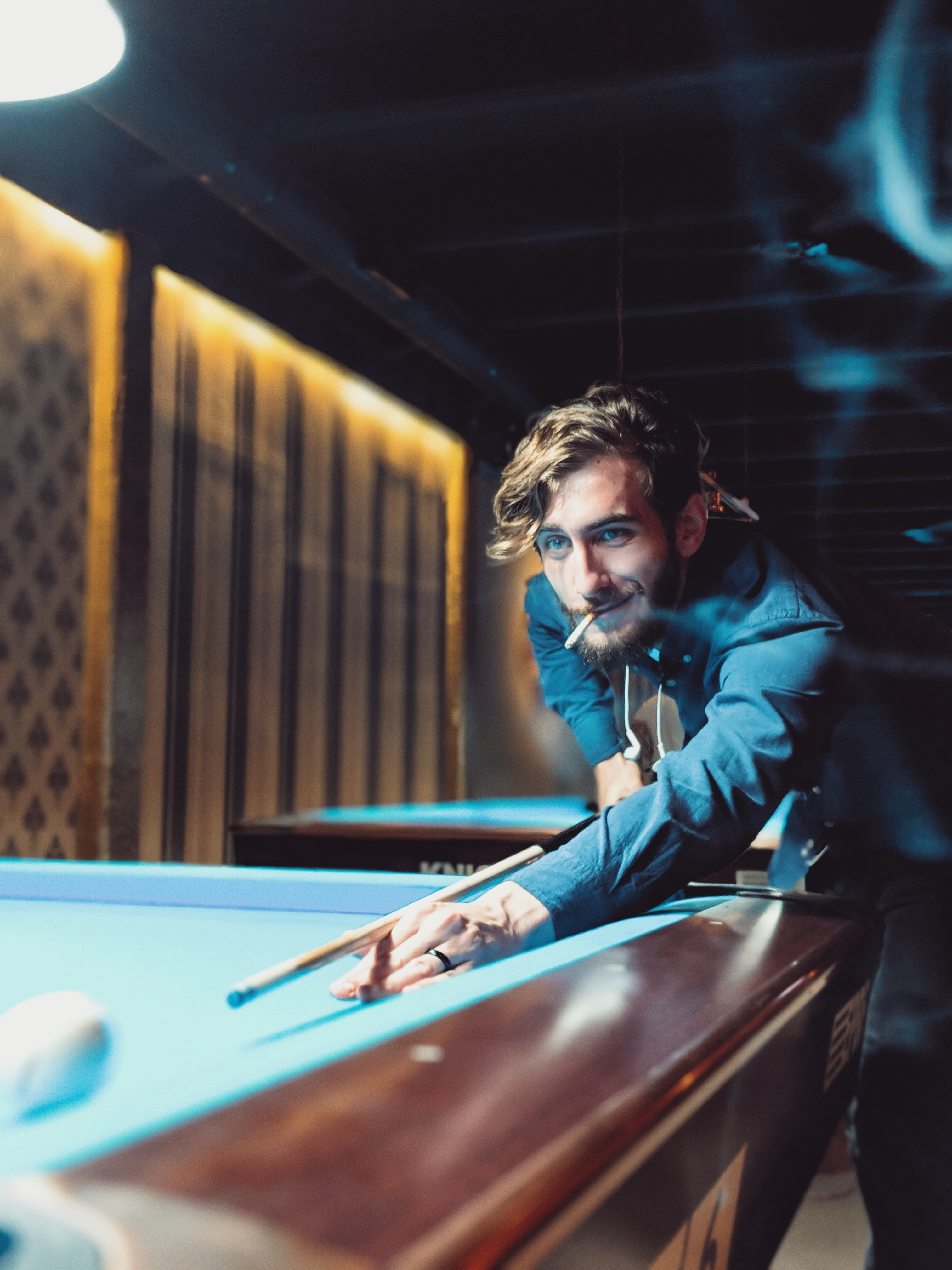 man smoking white playing billiard