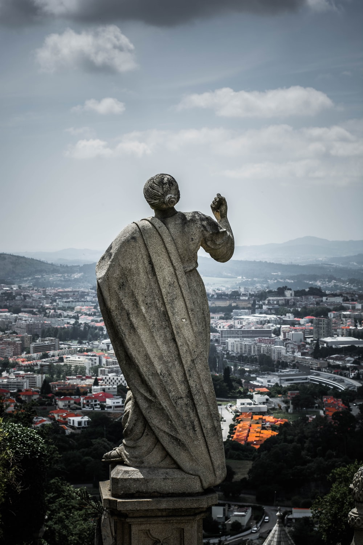 woman statue near village and mountain range under cumulus clouds