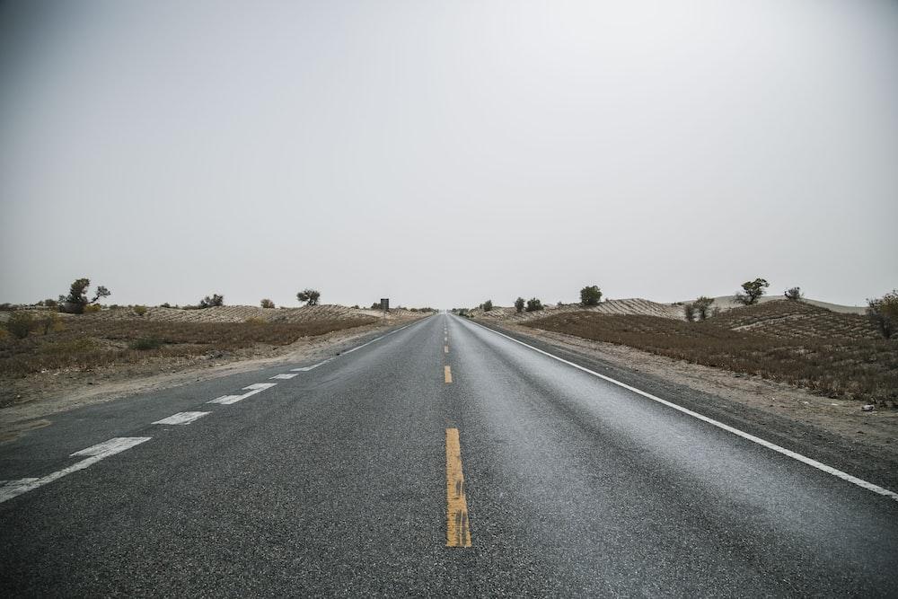 gray concrete road near gray soil