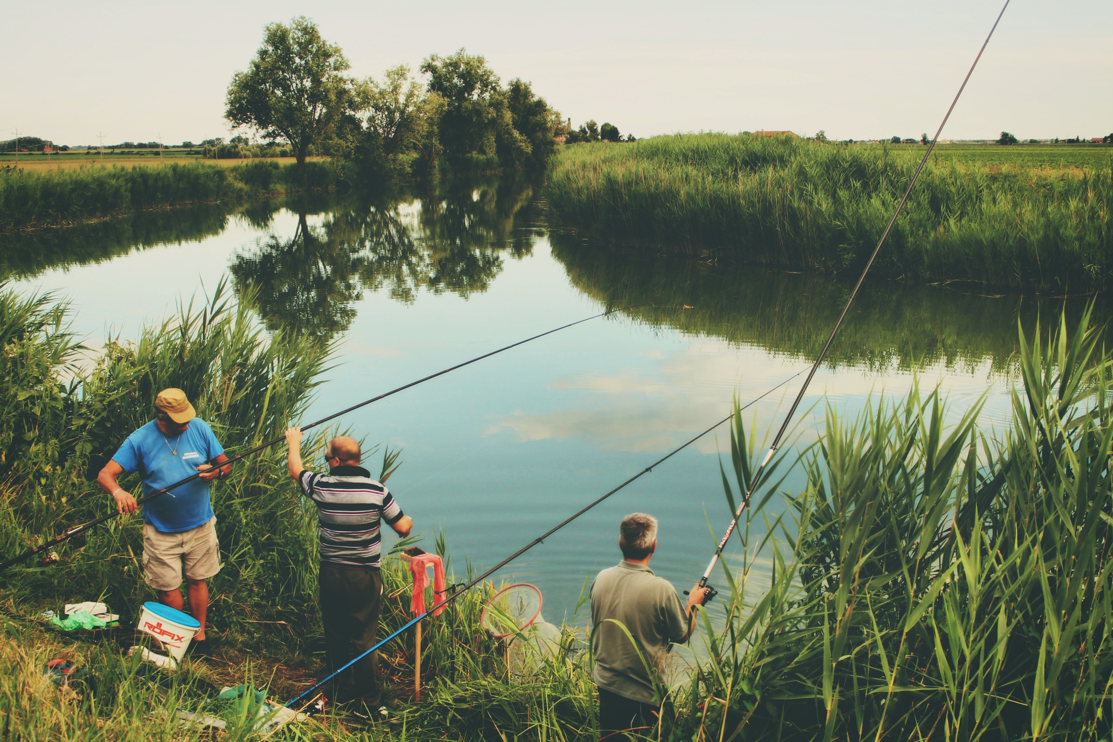 three men fishing during day