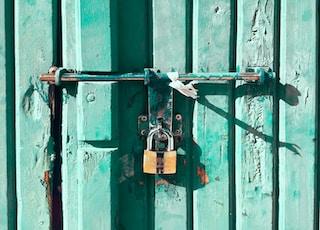 brown padlock on metal hinge