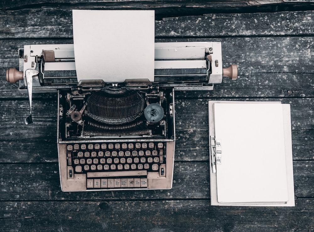 type writer beside clipboard on wooden surface