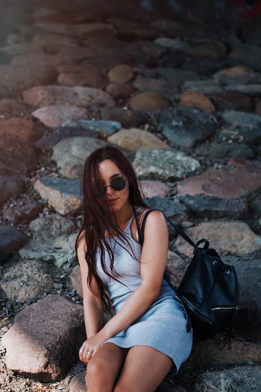 woman in gray mini dress sitting on rocks during daytime