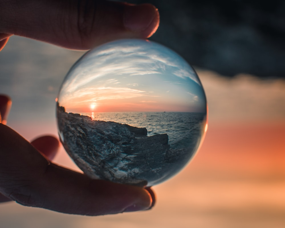 person holding round clear glass ball photo