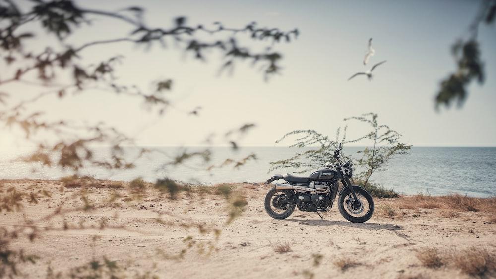 black and gray standard motorcycle on seashore