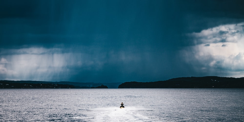 person riding watercraft at the middle of the sea