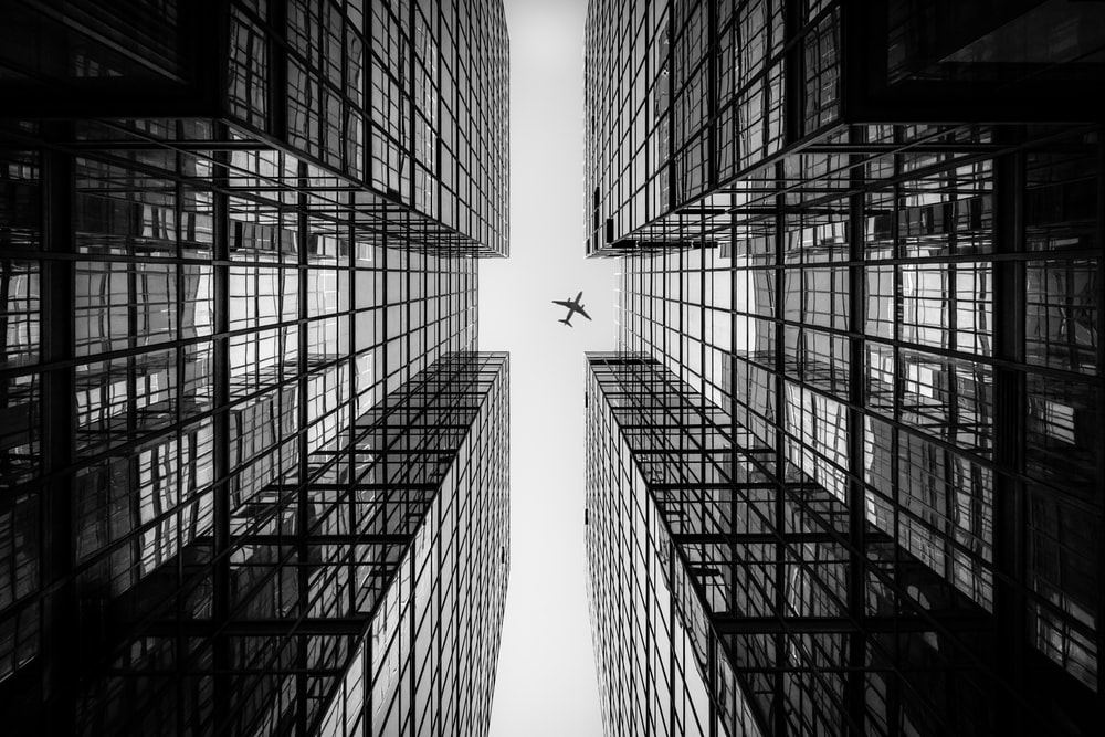 low angle photography of airplane passing above high-rise building