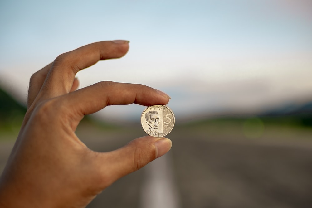 selective focus photography of person holding coin