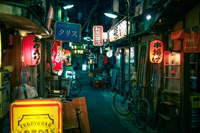 empty pathway in between stores tokyo teams background