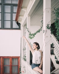 woman sitting on stair while raising right hand