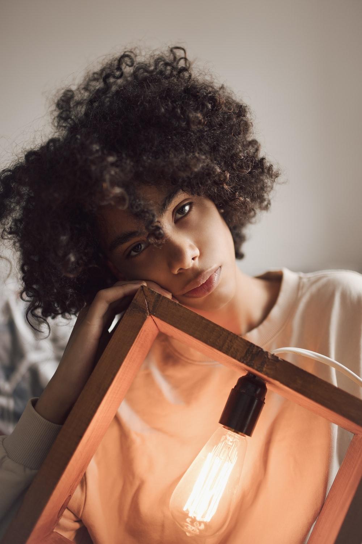 woman holding brown wooden framed light bulb