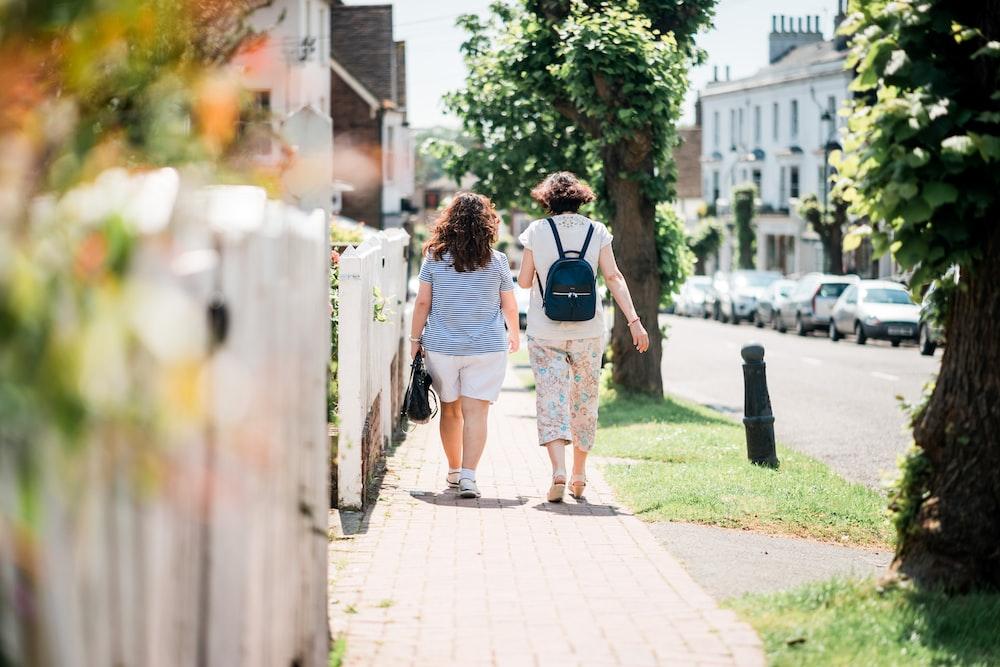 two women walking down sidewalk near fence