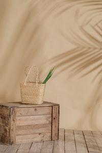 brown wicker basket on crate near wall
