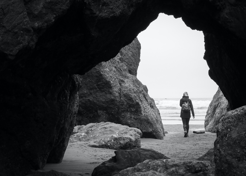 person walking beside rock formation near cave