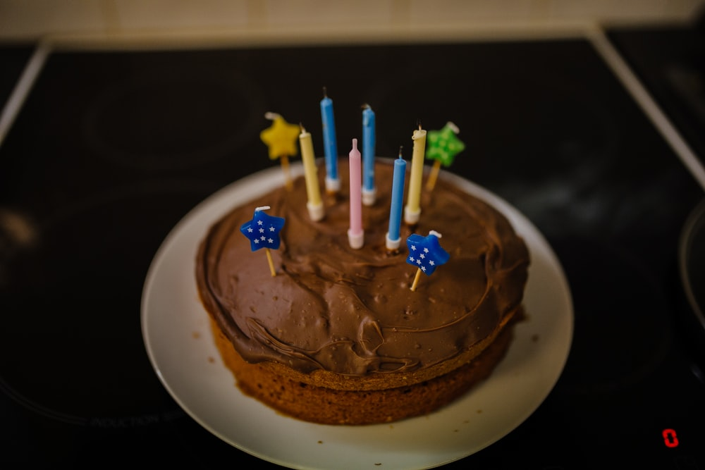 baked cake with candles on white plate