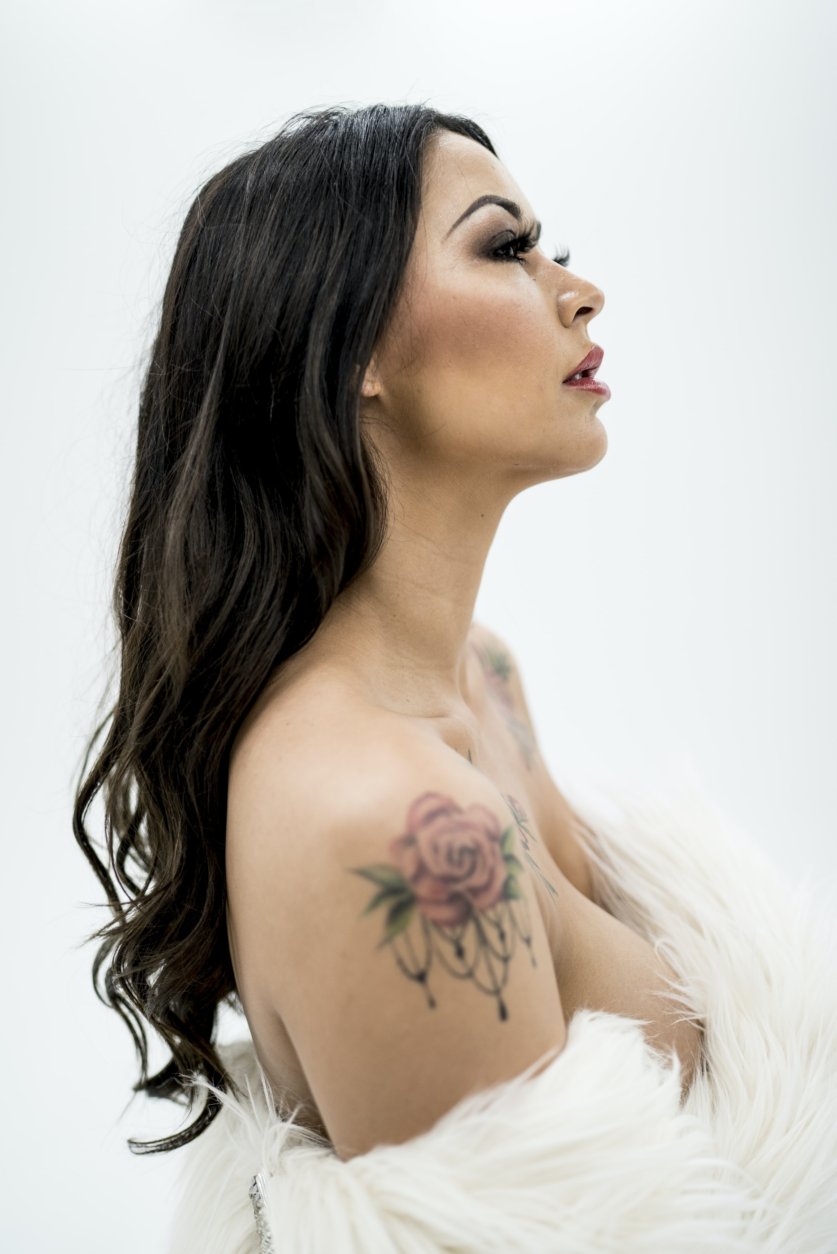 woman wearing white top with rose tattoo