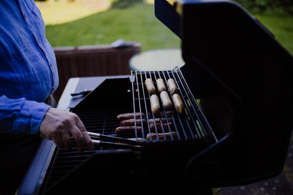 man grilling sausage during daytime