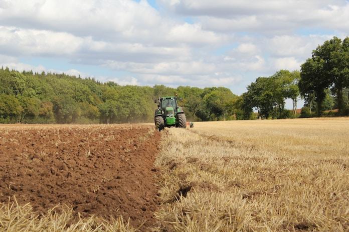 green tractor farming in field