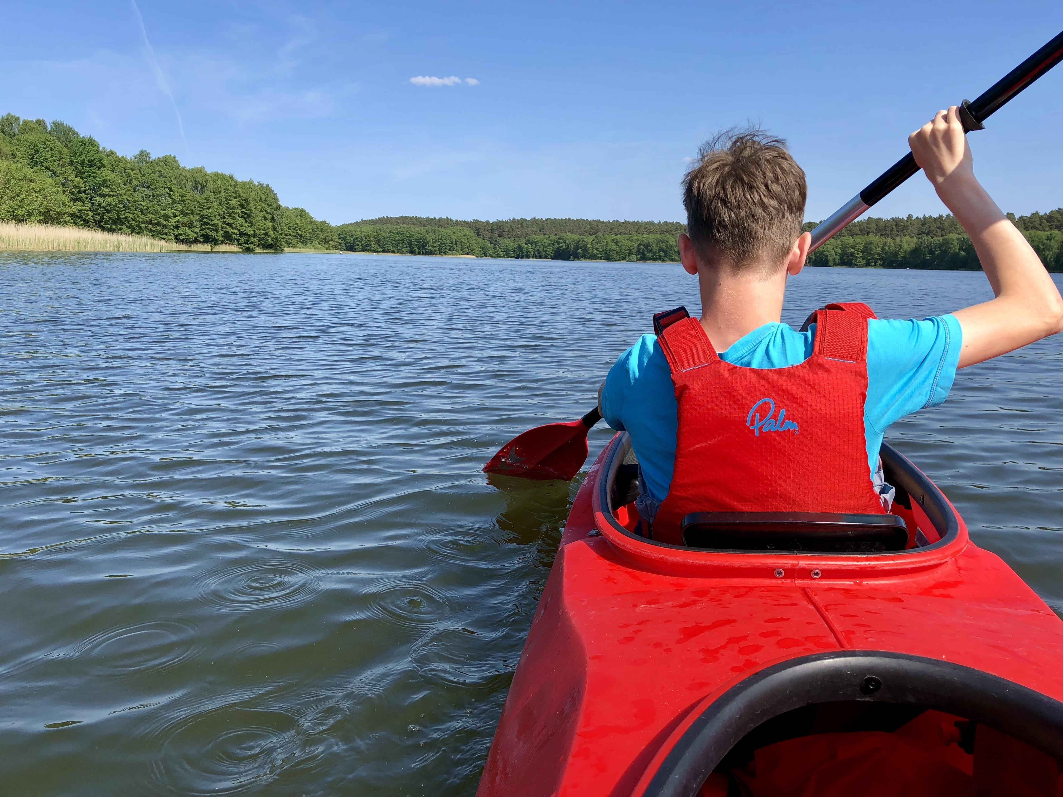 man paddling while riding kayak