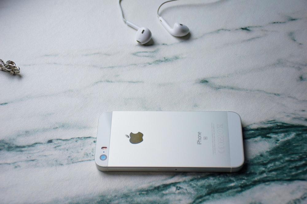 silver iPhone 5s beside EarPods