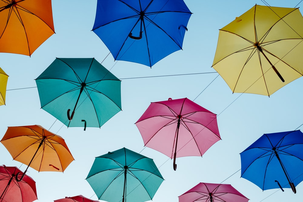 assorted-color umbrella hanging on gray wires