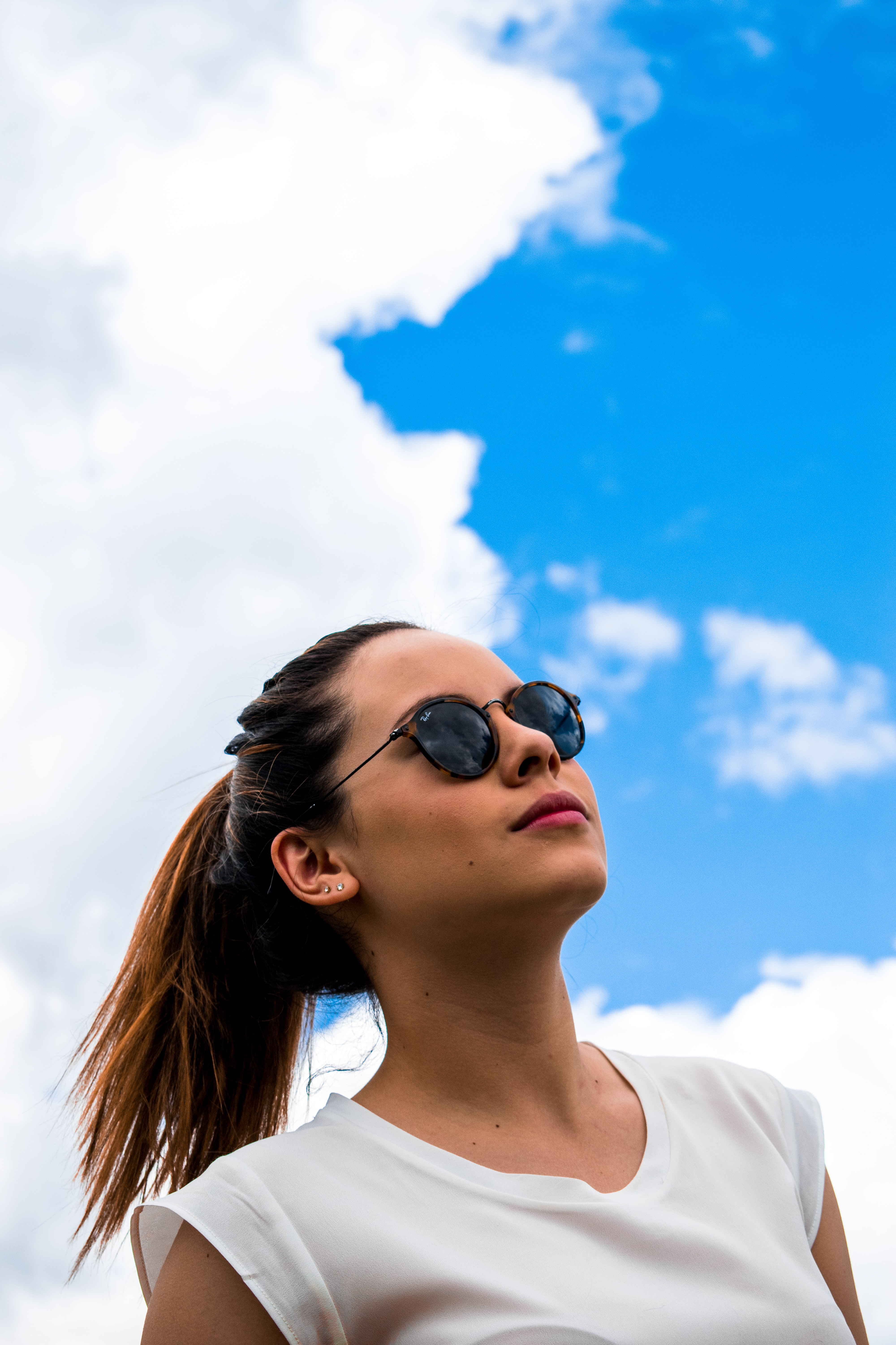 woman wearing brown Ray-Ban sunglasses looking at the sky