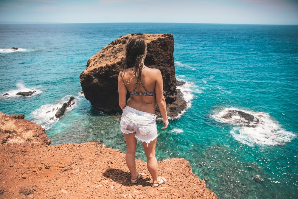 woman in white denim shorts standing on rock facing sea