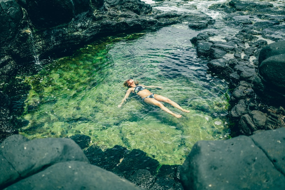 woman floating in body of water surrounded by stones