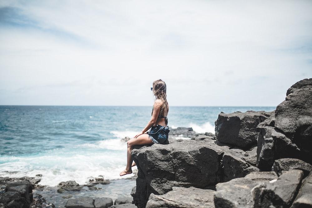 woman sitting on edge of rocks near sea