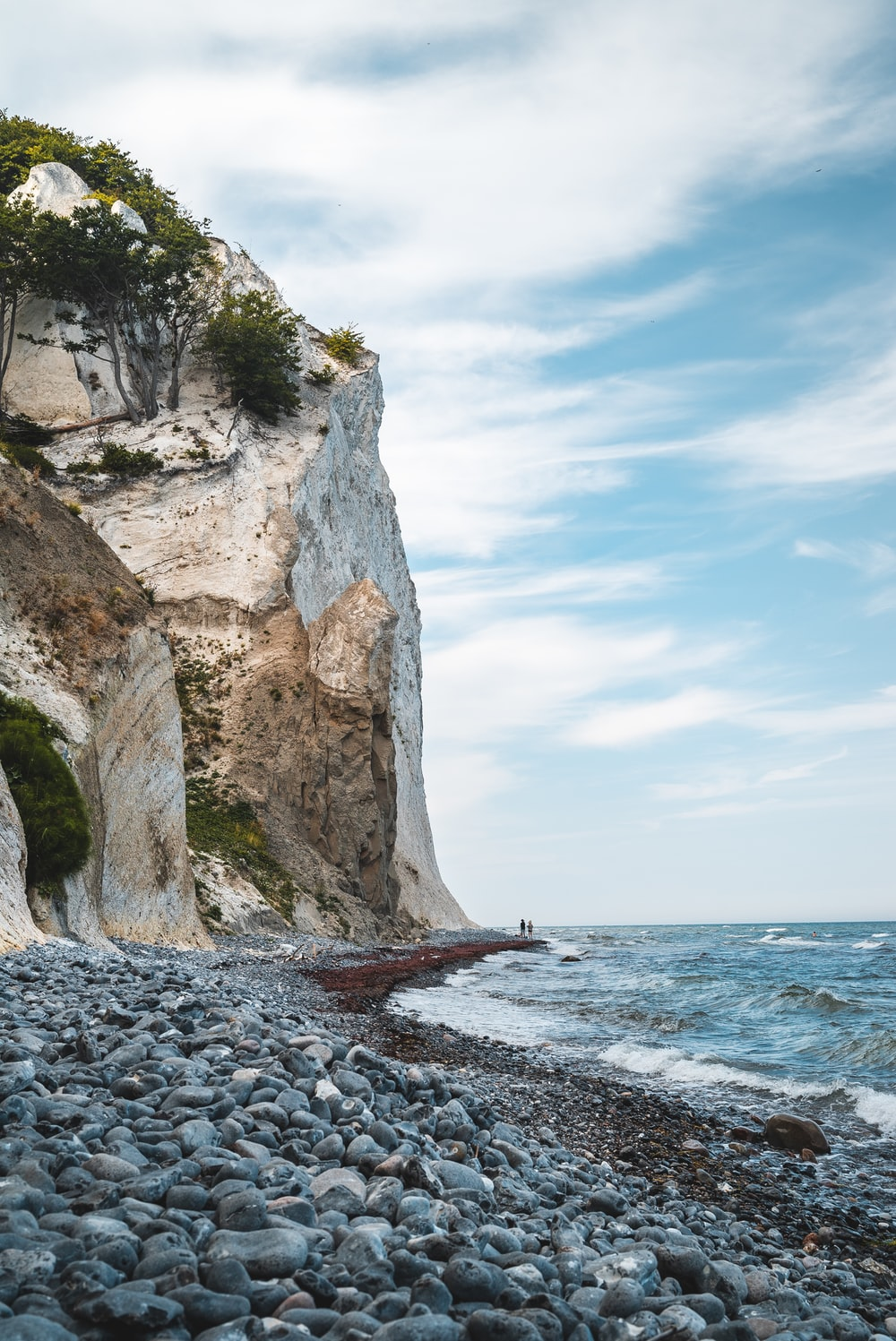 two person standing between cliff and body of water