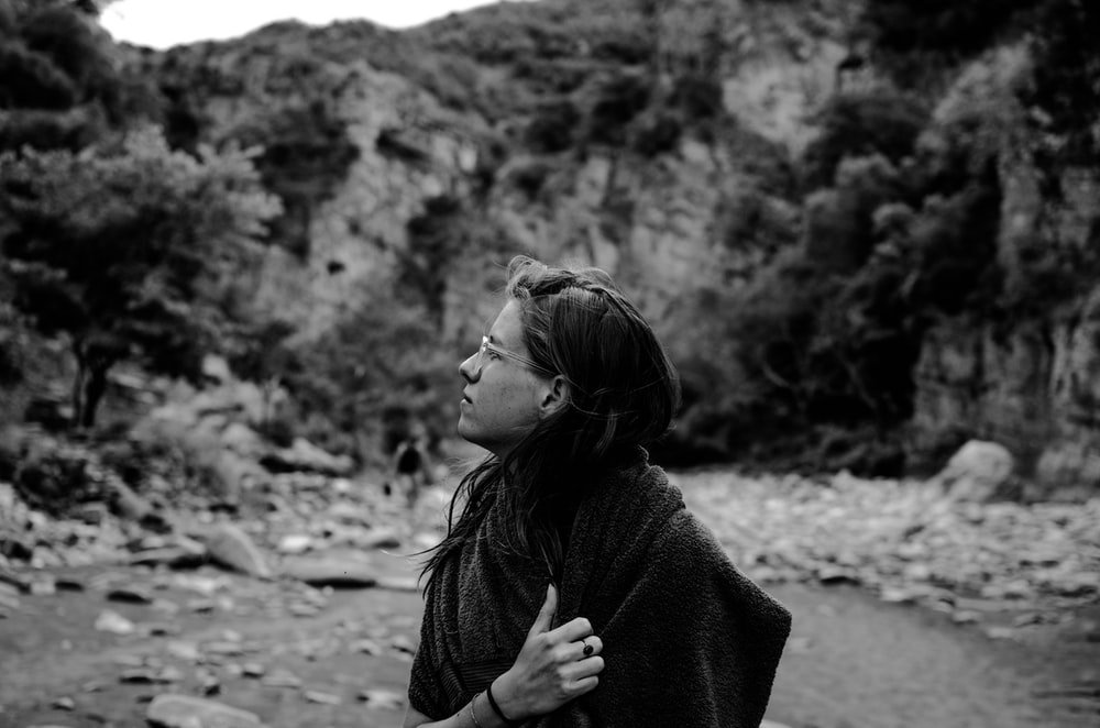woman standing beside river