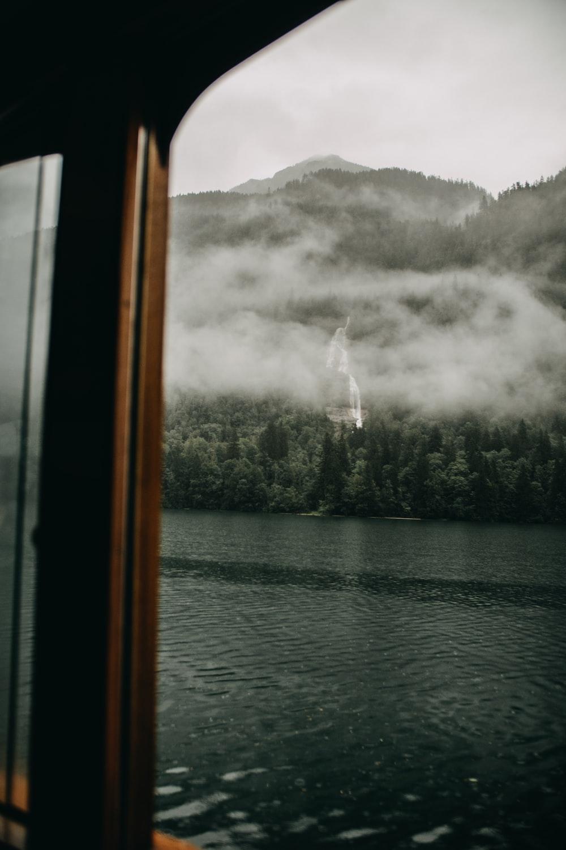 foggy green mountain near lake