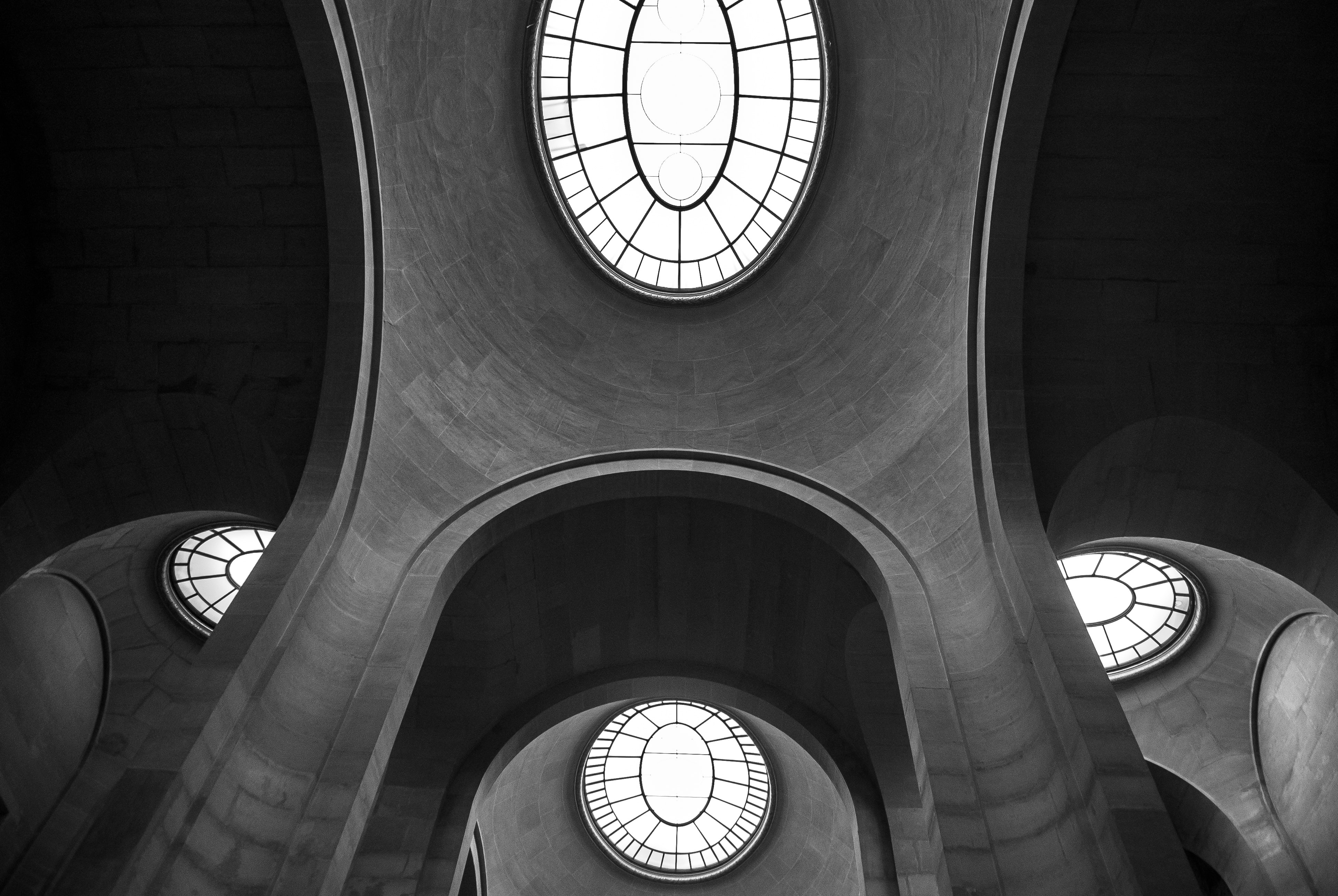 interior building with glass window at the roof grayscale photography