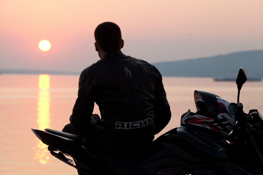 silhouette photo of man sitting on sports bike beside sea during golden hour