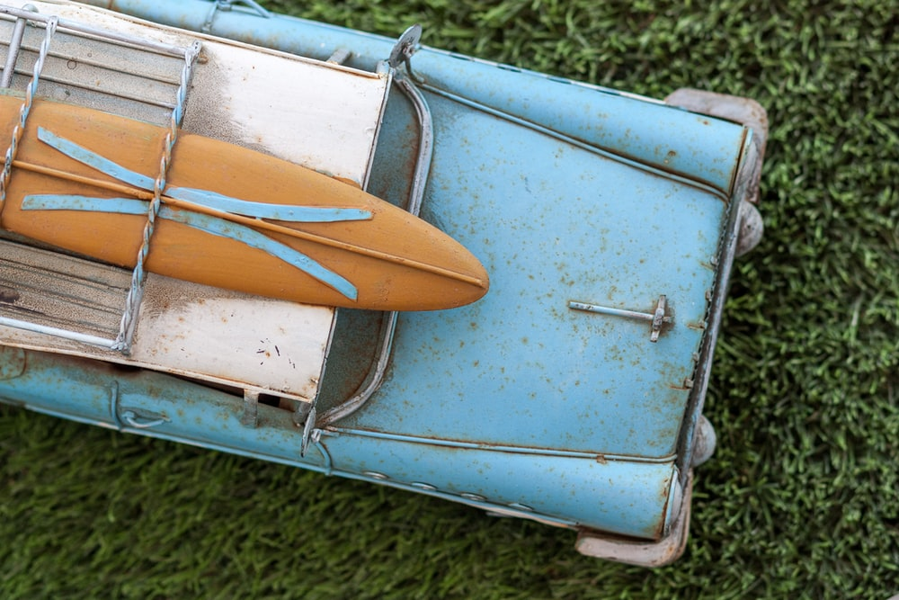 brown surfboard on rusted blue vintage car