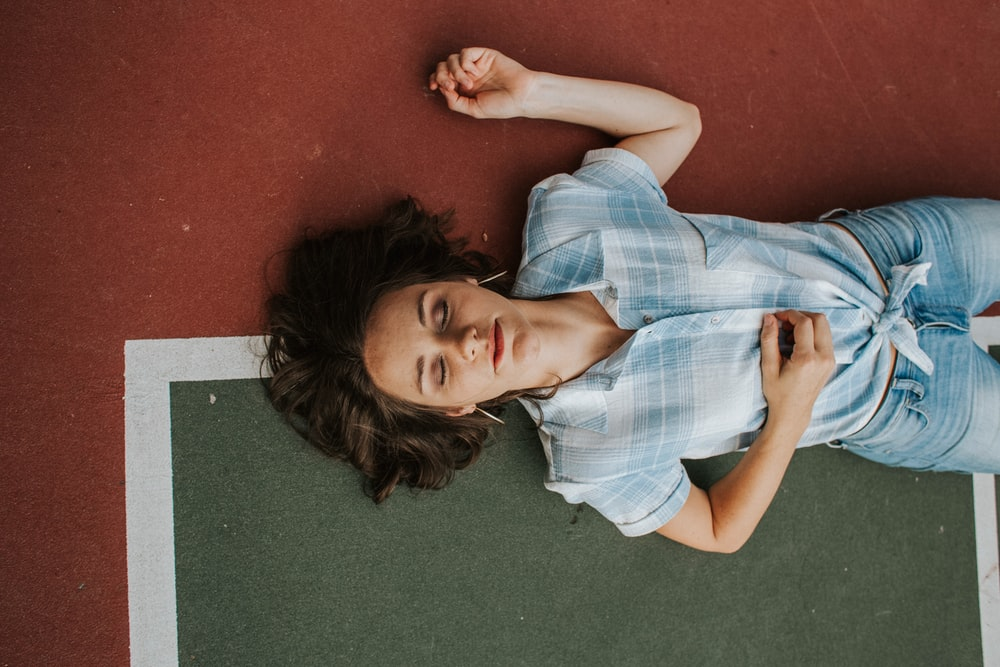 woman lying on floor while closing her eyes